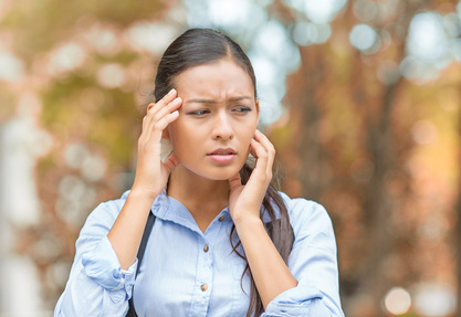 Stressed upset woman standing in park having headache